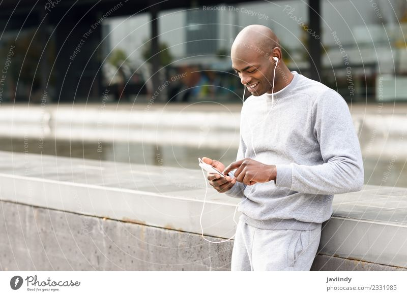 Black man listening to music with headphones outdoors Lifestyle Happy Music Sports Telephone PDA Technology Human being Masculine Young man Youth (Young adults)