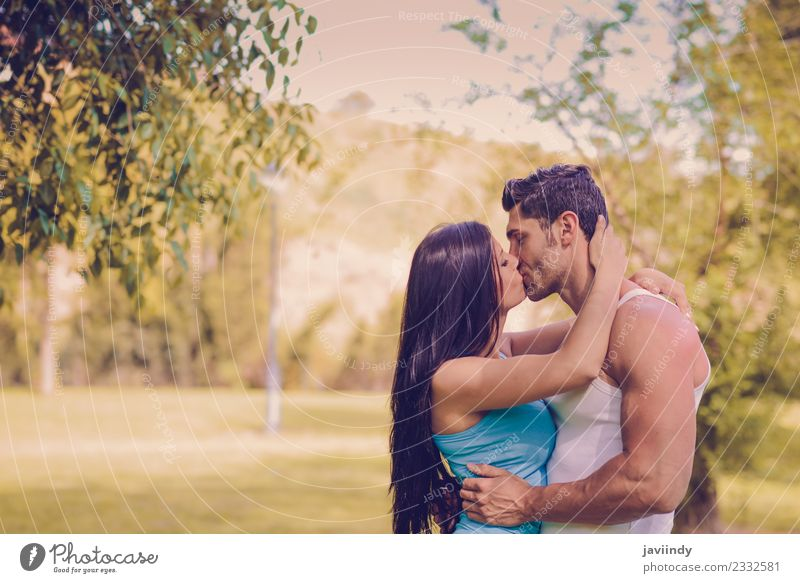 Young couple kissing in a urban park Woman Human being Nature Youth (Young adults) Man Young woman Young man Tree Joy 18 - 30 years Adults Lifestyle Love