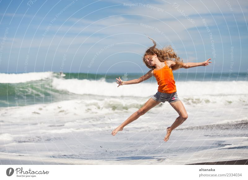 teen girl jumping on the beach at blue sea shore in summer vacation at the day time Lifestyle Joy Happy Beautiful Leisure and hobbies Playing Vacation & Travel