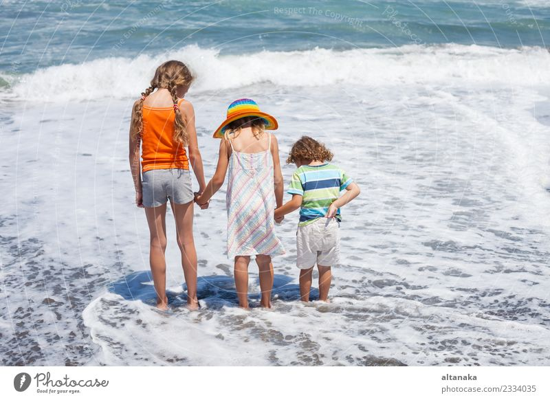 Three happy children playing on the beach at the day time. Concept of summer vacation. Lifestyle Joy Happy Beautiful Leisure and hobbies Playing