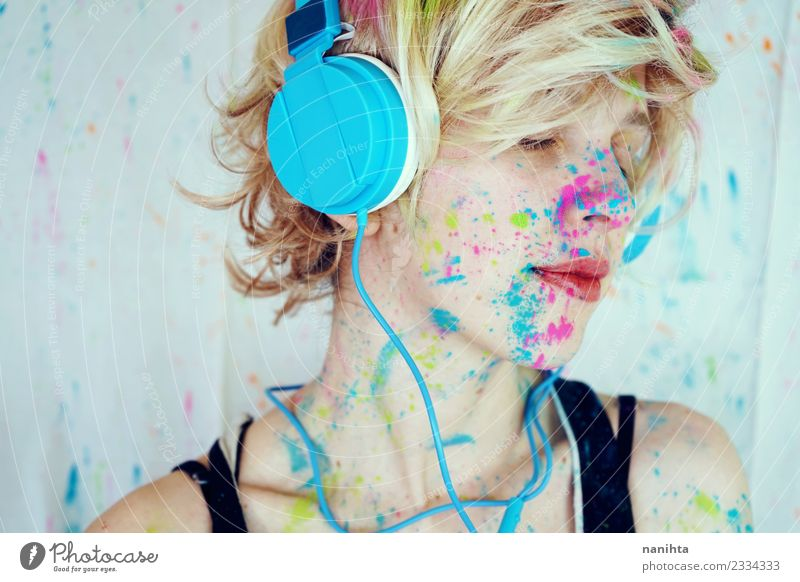 Young woman with paint in her face is listening to music Lifestyle Style Design Exotic Relaxation Calm Leisure and hobbies Technology Entertainment electronics