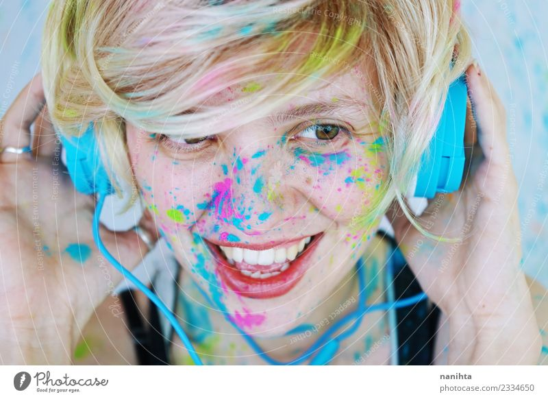 Young woman with paint in her face is listening to music Lifestyle Style Design Joy Beautiful Make-up Wellness Leisure and hobbies Human being Feminine