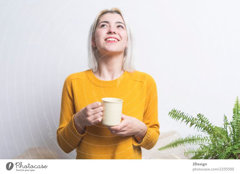 Happy young woman holding a cup of tea or coffee Breakfast Beverage Drinking Hot drink Coffee Espresso Tea Lifestyle Style Beautiful Face Health care Relaxation