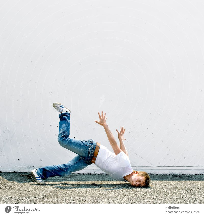 Human being Man Joy Adults Wall (building) Wall (barrier) Funny Healthy Facade Masculine Ground T-shirt Jeans To fall Pain Risk