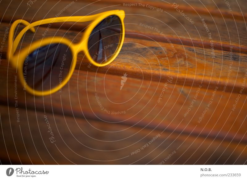 summer sunglasses Lifestyle Table Wooden table Sunglasses Brown Yellow Serene Summer Summer vacation Summery Colour photo Exterior shot Deserted