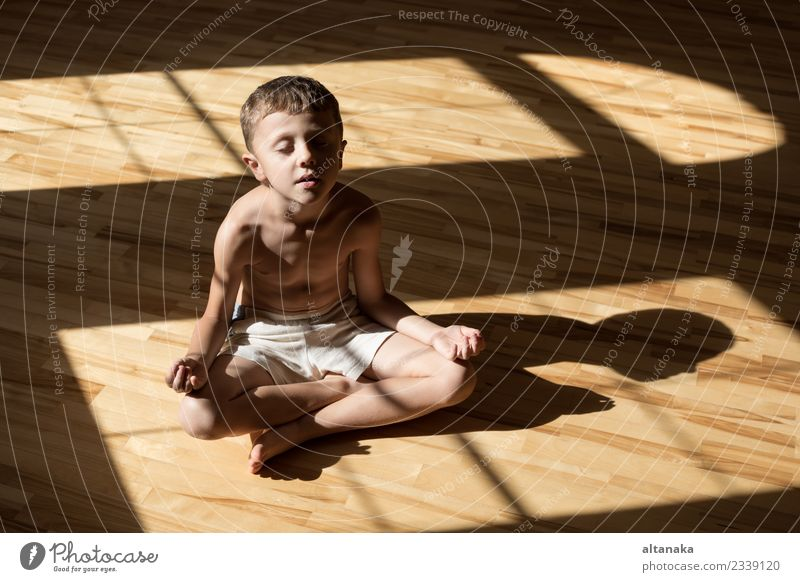 Charming little boy is while doing yoga at home Child Human being Man Hand Relaxation Joy Adults Lifestyle Sports Family & Relations Boy (child) Small Happy