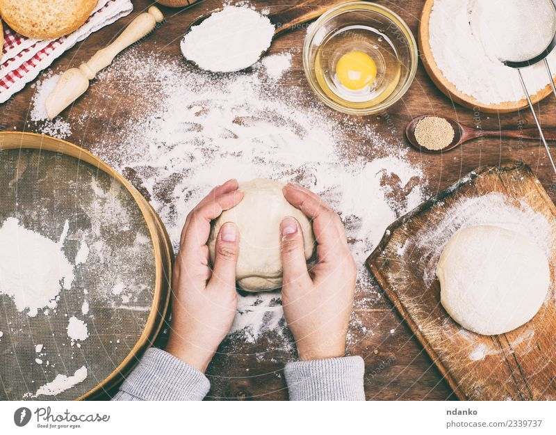 hands hold a ball of yeast dough Dough Baked goods Bread Bowl Table Kitchen Woman Adults Arm Hand 1 Human being 18 - 30 years Youth (Young adults) Sieve Wood