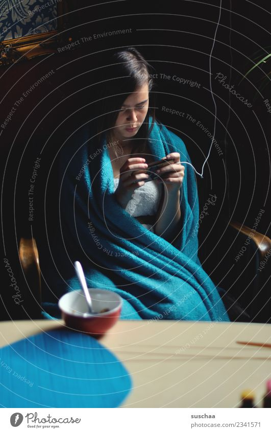 teenager sits at the breakfast table wrapped in a blanket and looks into her smartphone girl Child Youth (Young adults) Young woman 13 - 18 years Internet
