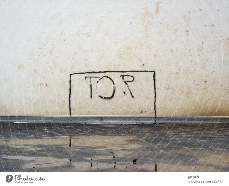 Tooor Playground Backyard Wall (building) Line Letters (alphabet) Playing field Sports Football pitch Shabby Goal Puddle Deserted Gloomy Water reflection