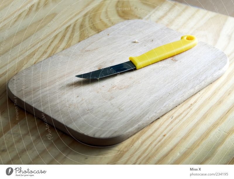chopping board Cutlery Knives Yellow Chopping board Wooden board Wooden table Kitchen Table Colour photo Interior shot Close-up Structures and shapes Deserted