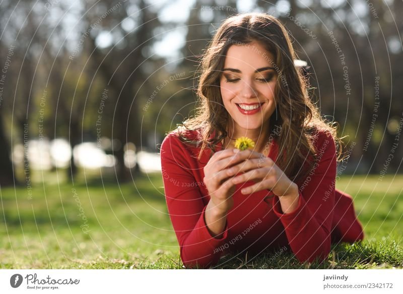 Young woman lying on grass in urban park. Woman Human being Nature Youth (Young adults) Summer Beautiful Flower Red Relaxation Joy 18 - 30 years Face Adults