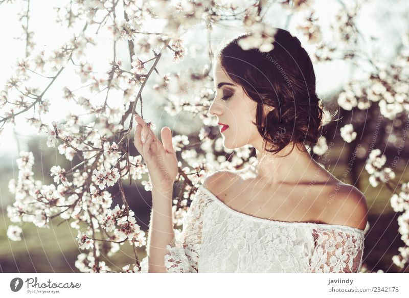 Young woman smelling almond flowers in springtime Style Happy Beautiful Hair and hairstyles Face Human being Woman Adults Nature Tree Flower Blossom Park