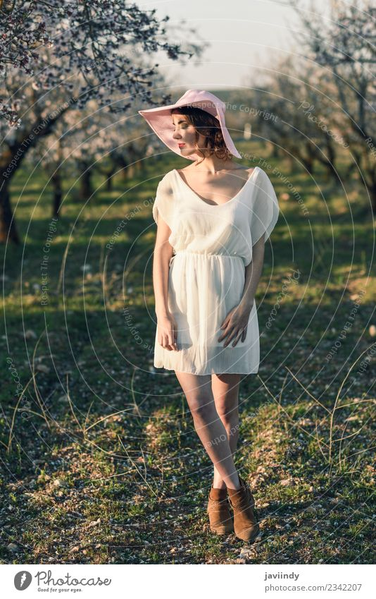 Young woman in almond flowered field in spring time Woman Human being Nature Youth (Young adults) Beautiful White Tree Flower 18 - 30 years Face Adults Blossom