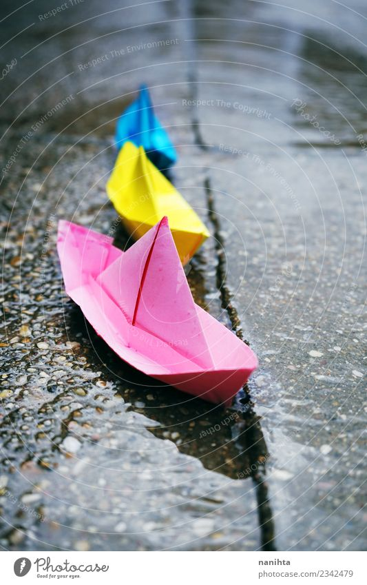 Color paper boats in a rainy day Blue Beautiful Water Street Yellow Pink Leisure and hobbies Rain Transport Retro Weather Growth Creativity Wet Paper Climate