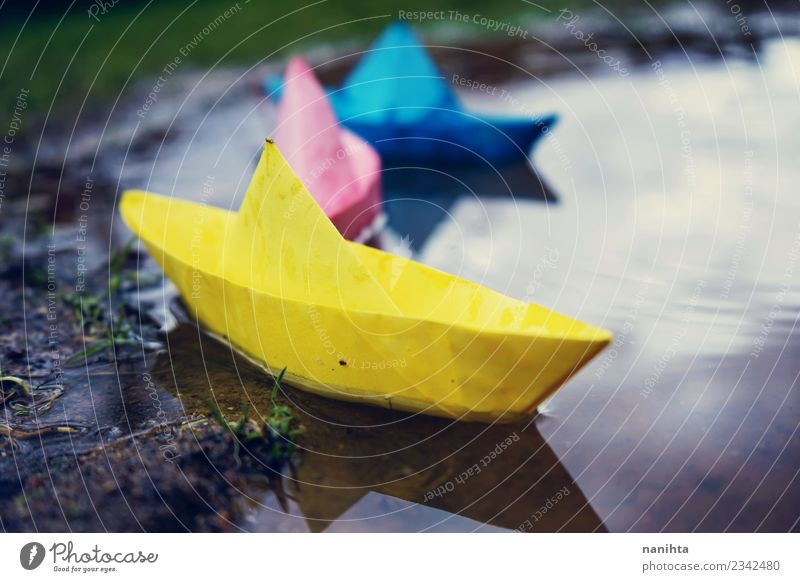 Color paper boats in a puddle Leisure and hobbies Playing Paper Paper boat Childhood memory Children's game Environment Nature Water Drops of water Climate