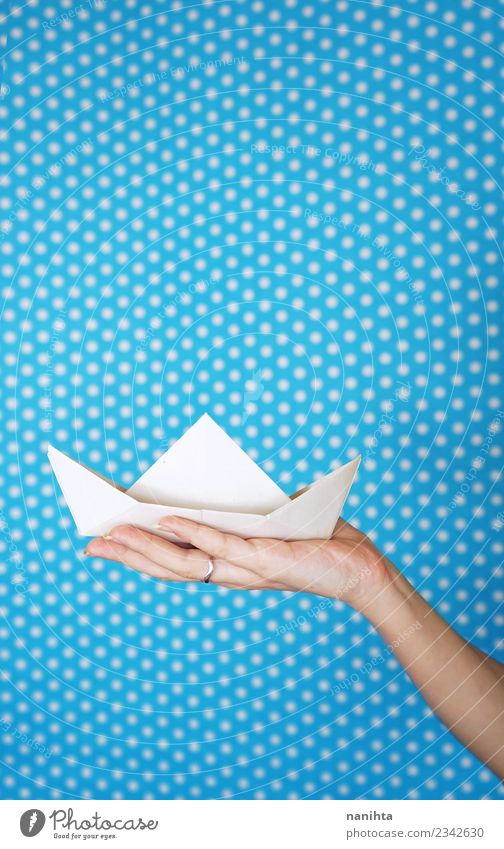 Hand holding a white paper boat against a blue background Vacation & Travel Blue White Background picture Playing Tourism Design Leisure and hobbies Contentment