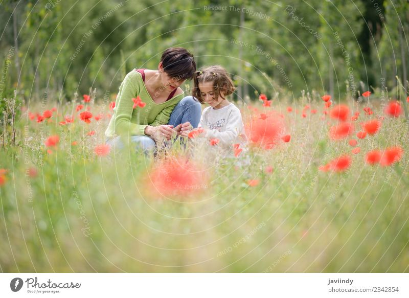 Happy mother with her little daughter in poppy field Lifestyle Joy Beautiful Playing Child Human being Girl Young woman Youth (Young adults) Woman Adults Mother