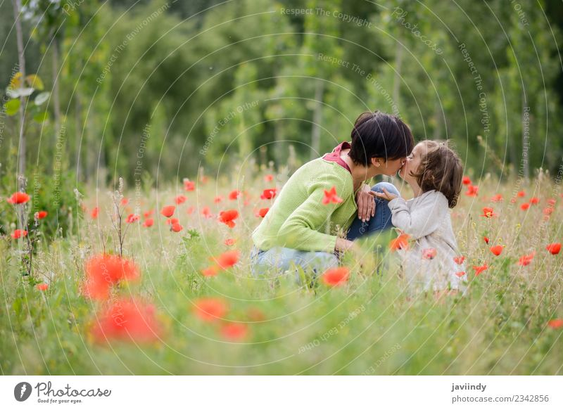 Happy mother kissing her little daughter in poppy field Woman Child Human being Nature White Flower Joy Girl Adults Love Meadow Family & Relations Grass Small