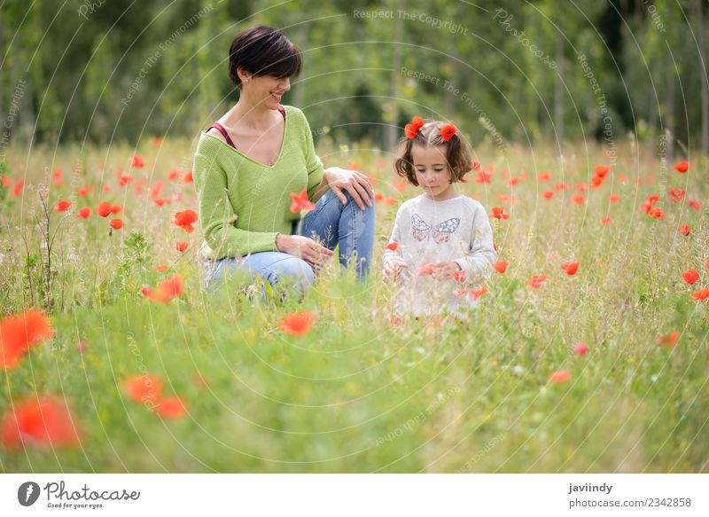 Happy mother with her little daughter in poppy field Lifestyle Joy Child Human being Girl Young woman Youth (Young adults) Woman Adults Mother