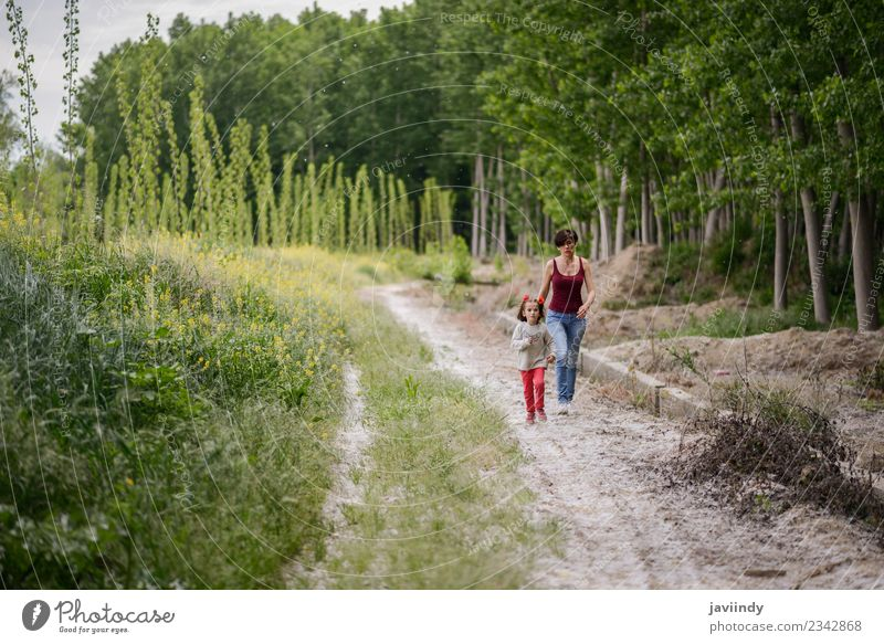 Happy mother with her little daughter in rural road. Woman Child Human being Nature Youth (Young adults) Flower Joy Girl Adults Lifestyle Meadow