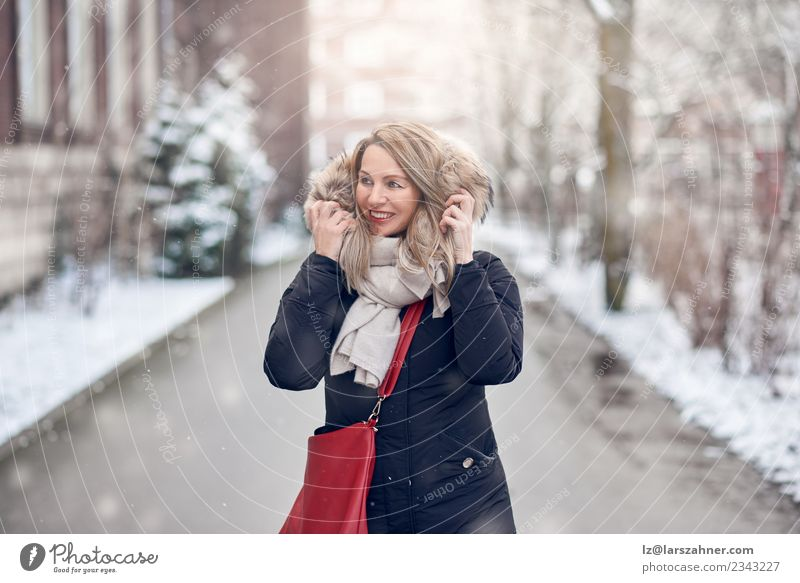 Smiling young woman walking along a snowy road Happy Beautiful Winter Snow Woman Adults 1 Human being 45 - 60 years Nature Weather Street Fashion Jacket Coat