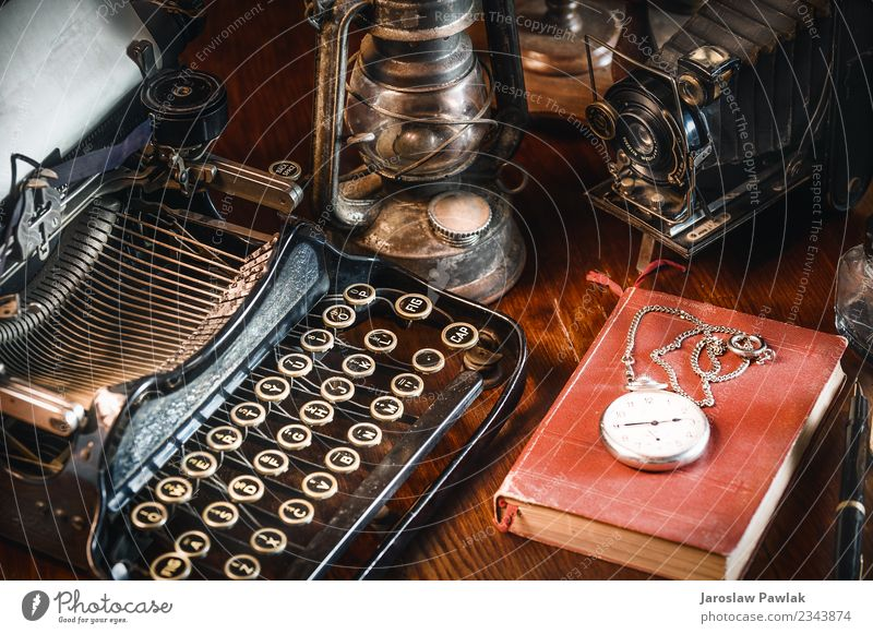 Traditional and old way of writing messages and taking photos, typewriter, camera, watch, pen, Vintage lamp on the desk White ancient antique background black