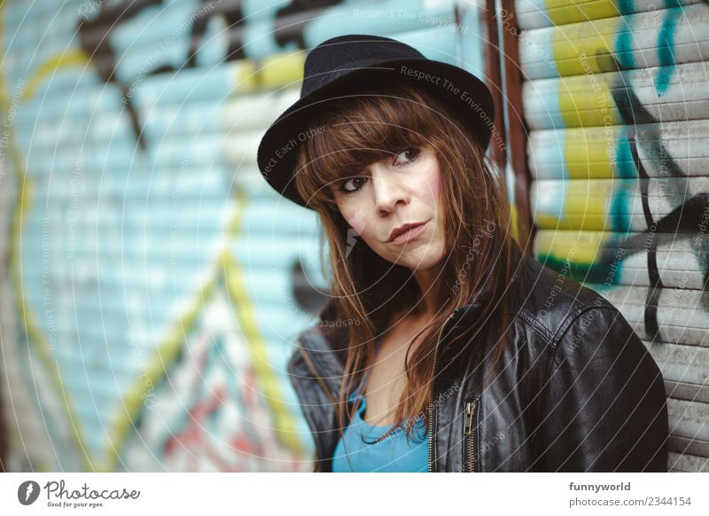 Woman stands before Graffiti and looks seriously to the side Human being Feminine Adults 1 30 - 45 years Cool (slang) Town Hat Bangs Brunette Skeptical Observe