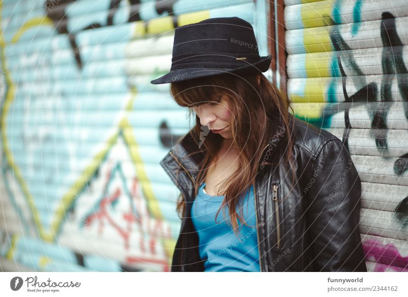 Woman standing in front of graffiti looking down. Feminine Adults 1 Human being 30 - 45 years Hat Cool (slang) Long-haired Leather jacket Graffiti Town Sadness