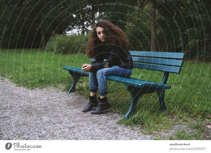 Young woman sitting on park bench Human being Feminine Youth (Young adults) Woman Adults 1 13 - 18 years Garden Park Jeans Jacket Brunette Long-haired Curl Sit