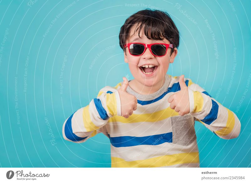 smiling boy with sunglasses on blue background Child Human being Joy Lifestyle Funny Emotions Laughter Boy (child) Happy Party Feasts & Celebrations Masculine