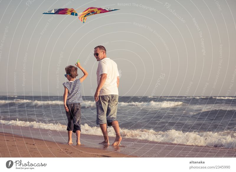 Father and son playing on the beach at the day time. Child Sky Vacation & Travel Man Summer Hand Relaxation Joy Beach Adults Life Lifestyle Love Sports