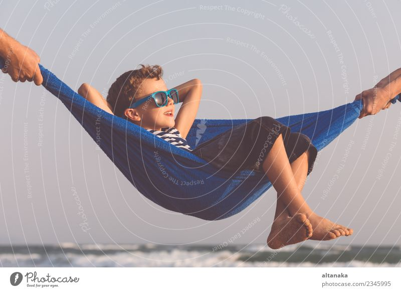 Happy little boy relaxing on the beach at the day time. Child Human being Nature Vacation & Travel Man Summer Sun Hand Ocean Relaxation Joy Beach Adults