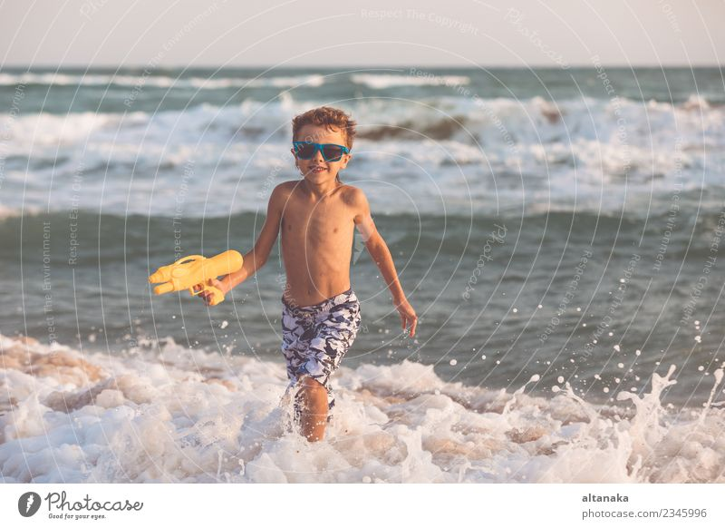 Happy little boy relaxing on the beach at the day time. Lifestyle Joy Beautiful Relaxation Leisure and hobbies Playing Vacation & Travel Trip Adventure Freedom