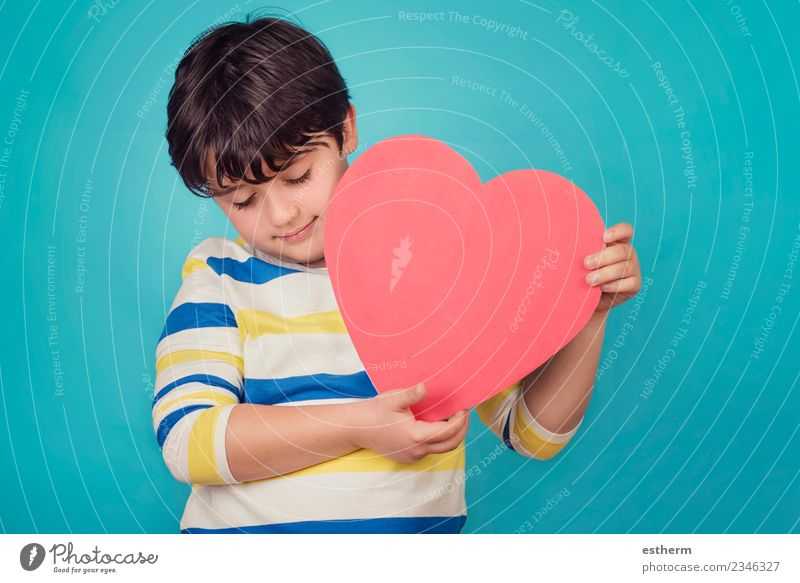 smiling boy with a heart on blue background Child Human being Joy Lifestyle Love Family & Relations Boy (child) Party Feasts & Celebrations Together Friendship