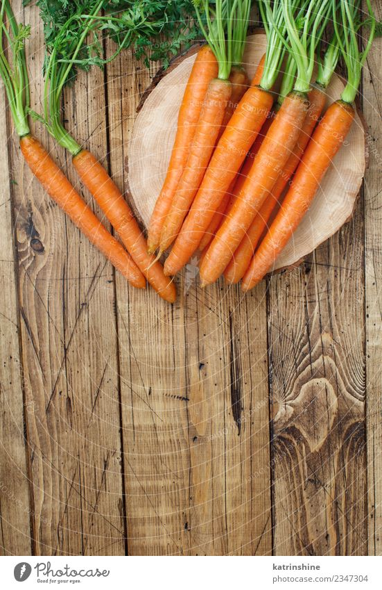 Fresh raw carrots with leaves on a wooden table Vegetable Nutrition Vegetarian diet Leaf Brown Green Carrot Farmer food Harvest healthy market orange Organic