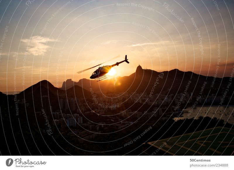 A helicopter flows into the sunset in Rio de Janeiro Landscape Beautiful weather Mountain Brazil Capital city Port City Skyline Tourist Attraction Landmark
