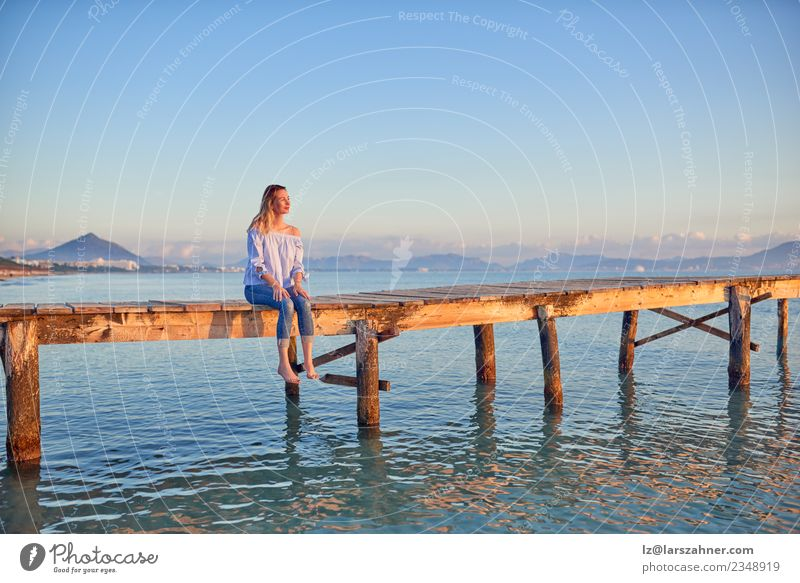 Barefoot woman sitting on a coastal pier at sunset Lifestyle Happy Beautiful Leisure and hobbies Vacation & Travel Freedom Summer Sun Beach Ocean Woman Adults