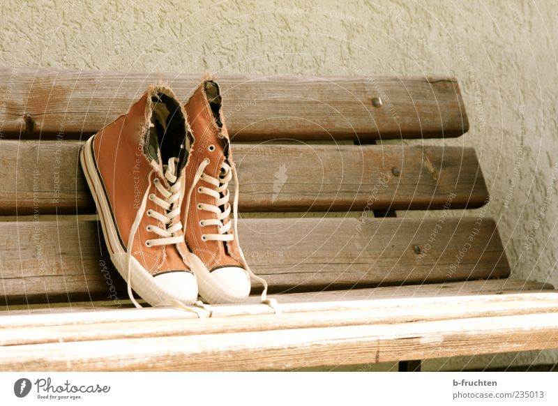 Cloth shoes on a park bench, antique look Design Wall (barrier) Wall (building) Footwear Sneakers cloth shoe Wood Old Dirty Brown Loneliness lace-up shoe
