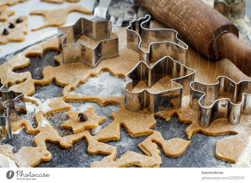Cooking Christmas cookies with cookie cutters on a dark table White Winter Brown Metal Kitchen Tradition Dessert Make Baked goods Dough Snowflake Festive Raw