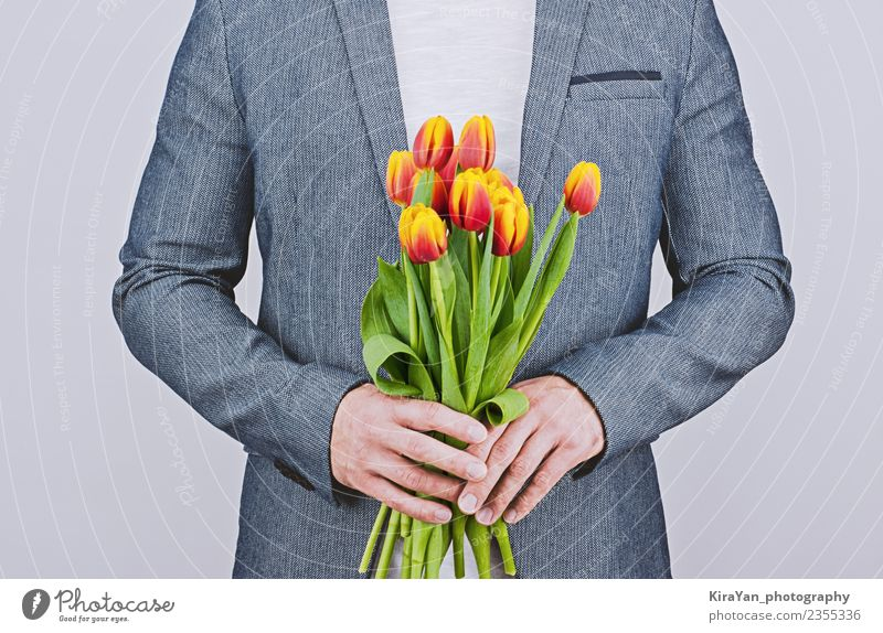 Man in blue jacket holding bouquet of tulips Human being Blue Beautiful White Flower Red Adults Yellow Love Happy Feasts & Celebrations Copy Space Gift Mother