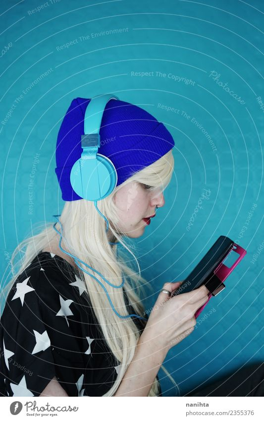 Young woman listening to music with her headphones and phone Lifestyle Style Design Hair and hairstyles Leisure and hobbies Cellphone MP3 player Technology