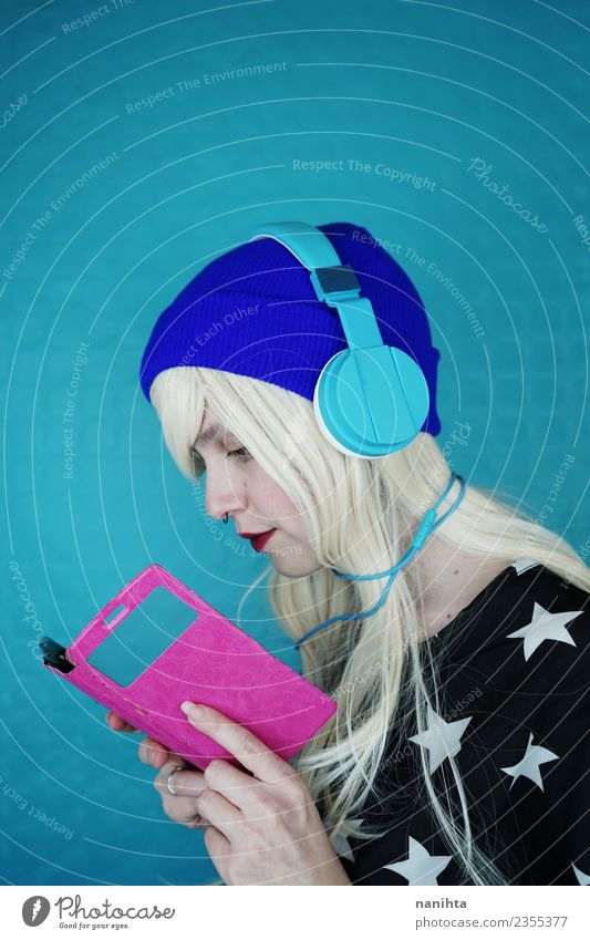 Young woman reading and listening to music with her phone Lifestyle Style Hair and hairstyles Leisure and hobbies Cellphone Headset Cable Technology