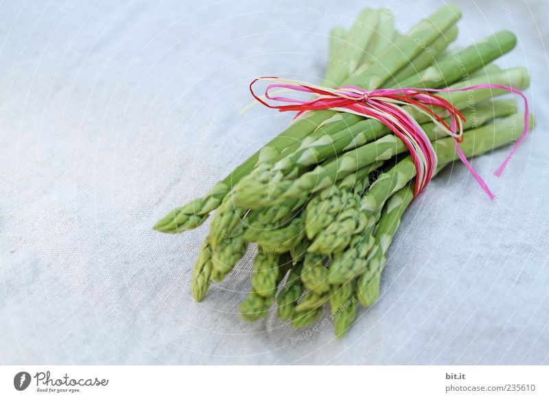 A portion of green asparagus tips, freshly harvested from the local field, tied together, decorated with a ribbon with a bow, made of raffia, on the table with white linen cloth.
