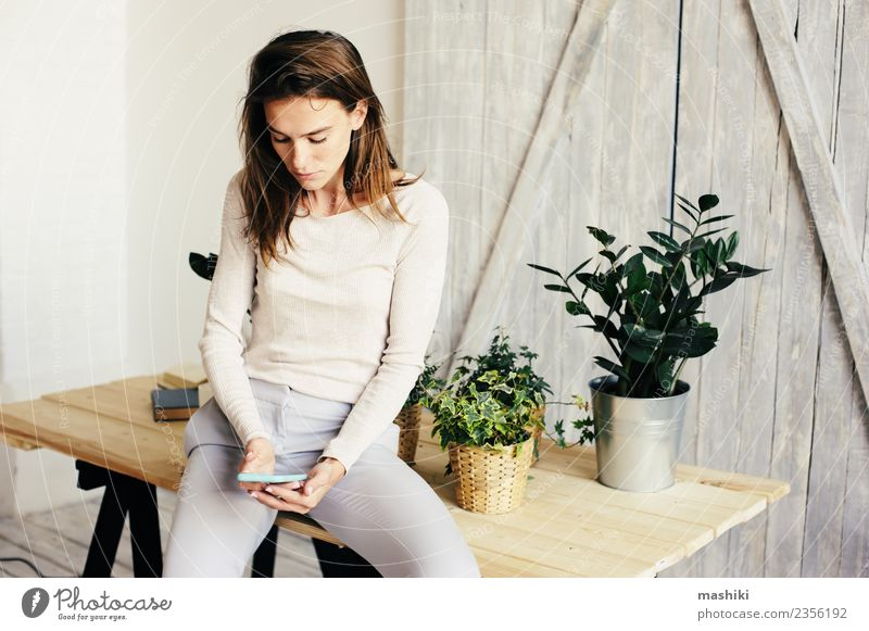 young woman texting message Woman Plant Flower Adults Lifestyle Fashion Modern Table Model Living room Flowerpot Trend Gardener Houseplant