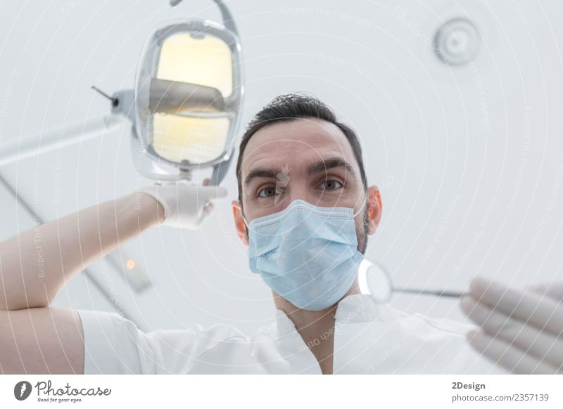 Dentist leaned over patient in dentist's chair at clinic. Health care Medical treatment Medication Profession Doctor Tool Human being Masculine Young man