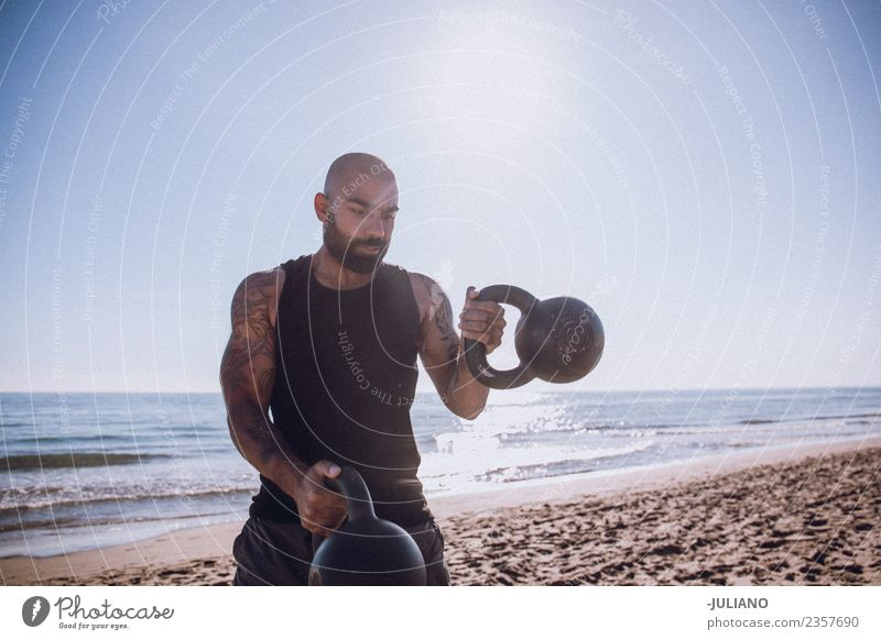 Sports man is doing kettle bells workout at the beach Young man Beach Fitness Sports Training Professional training Hard Perspire Musculature Joy Sportsperson