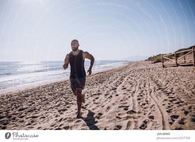 Young sports man is doing running workout at the beach Young man Sports Beach Fitness Sports Training Hard Perspire Musculature Joy Sportsperson Speed Positive