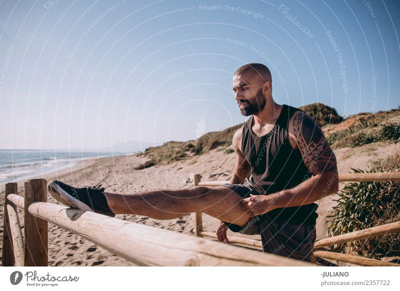 tough muscular man is doing stretching at railing to beach Young man Sports workout Beach Fitness Sports Training Hard Perspire Musculature Joy Sportsperson