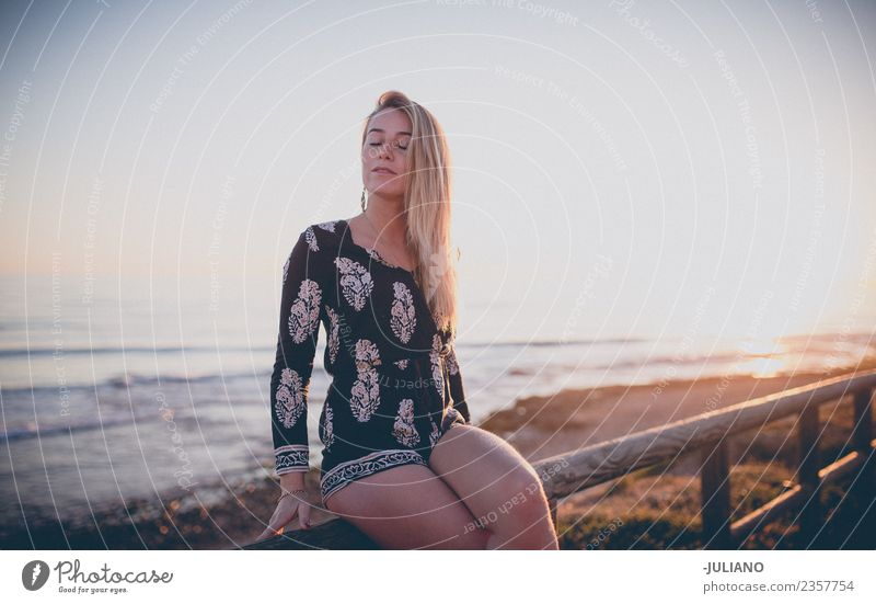 Young Girl is sitting enjoying the view of the sunset at ocean Sun Beach Blonde Cool (slang) Dusk Joy girl Goodness Laughter Lifestyle Ocean Retro Sand Smiling