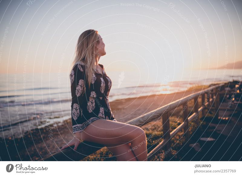 Young woman sitting on railing watching the sunset at the ocean Sun Beach Blonde Cool (slang) Dusk Joy Girl Good Goodness Laughter Lifestyle Ocean Retro Sand
